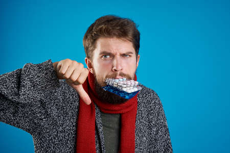 A man with a beard and warm clothes keeps a lot of blisters in his mouth and does not approve of it. Stock Photo