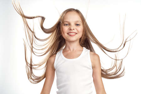 young girl in a white T-shirt with flying hair on a light background. Stock Photo
