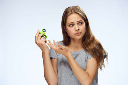 a girl in a gray T-shirt is holding a green spinner in her hand and slightly perplexed.