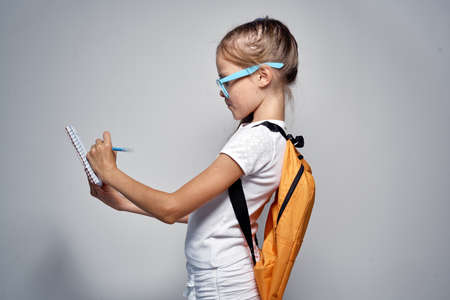 the child writes in a notebook in glasses and with a backpack on a light gray background. Stock Photo