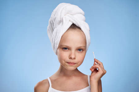 little girl in towel on head with cotton swab on blue background.