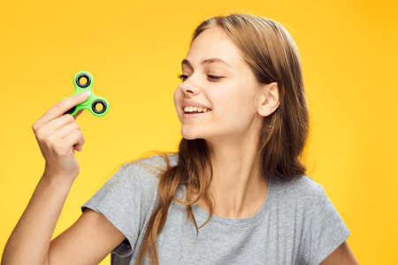 Young beautiful woman on a yellow background holds a fidget spinner.