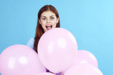 beautiful woman with an armful of balloons, emotions, light blue background.
