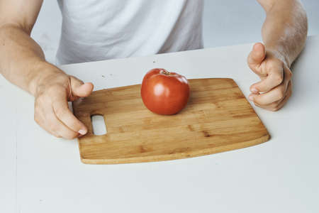 table, hands, wooden board, tomato, close-up.