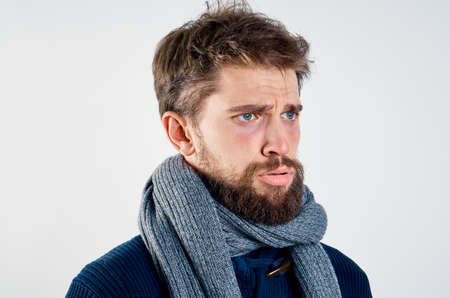 sick man in a scarf, sweater, emotions, cold, light background, portrait.