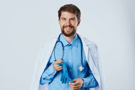 male doctor smiling and holding gloves in hands. Stock Photo