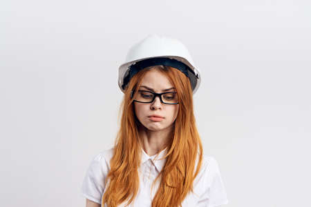 red-haired woman in helmet on light background.