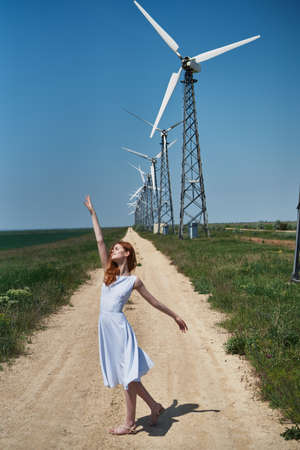 woman in a light dress against the background of windmills.
