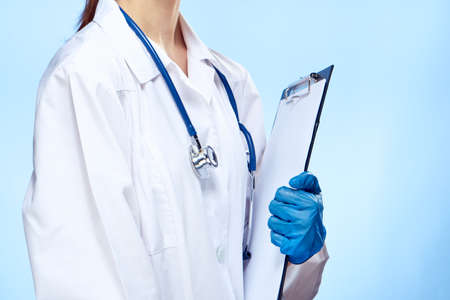 female doctor holding a folder in his hand, stethoscope, close-up, light blue background.