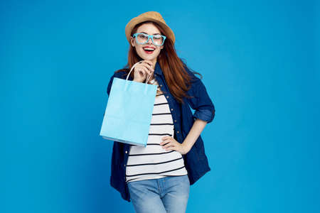 young woman, hat, glasses, package, shopping, blue background.