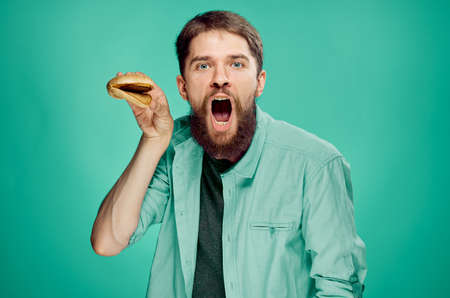 bearded man with an open mouth, burger, green background. Stock Photo