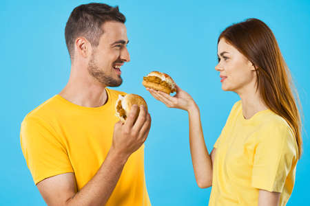 Cheerful young couple in yellow t-shirts hamburger fast food