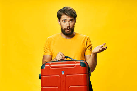 A man in a yellow T-shirt holds in his hand a red suitcase 版權商用圖片 - 150638102