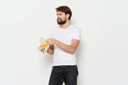 A man in a T-shirt and pants with potatoes