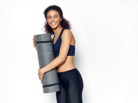 Happy athletic woman with fitness mat laughing