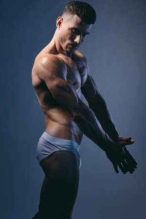 sexy man with muscular muscles on a gray background Imagens