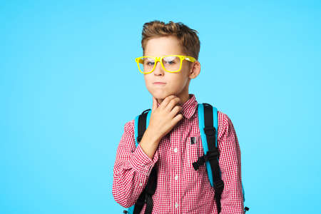 Puzzled by schoolchildren with a backpack on their back and yellow glasses