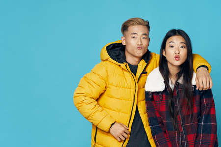 Man in a yellow jacket Asian appearance and woman air kiss