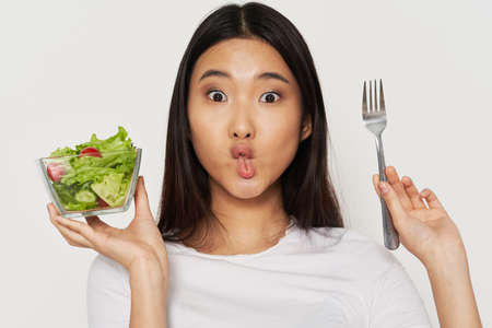 woman with a plate of salad and with a fork grimaces