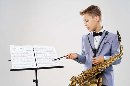 A boy in a classic suit with a saxophone considers notes