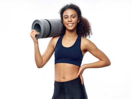 Happy slim woman with fitness mat beautiful model