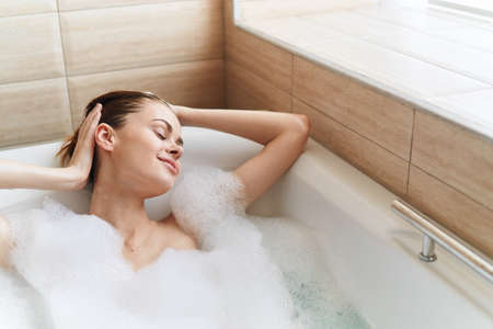 Happy woman enjoys relaxing in the bathroom and white foam
