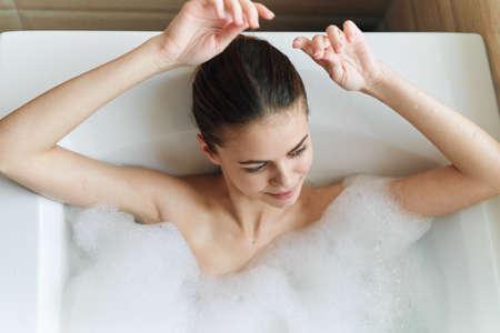 Woman in bathtub with white foam top view clean skin cosmetology Reklamní fotografie - 151445443