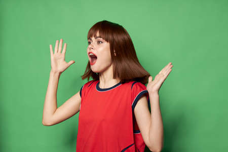 admired woman on a green background in a red T-shirt gesticulates with her hands Imagens
