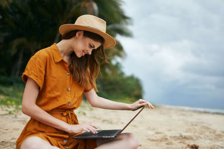 Beautiful woman with a laptop sits on the sand and works Archivio Fotografico