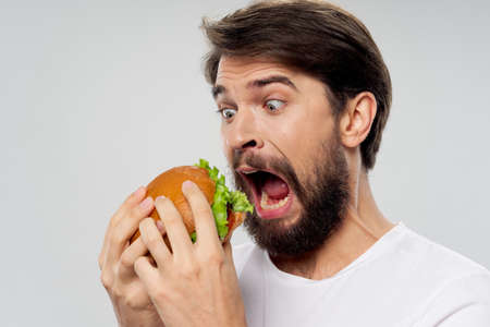 A hungry man with a huge hamburger opened his mouth wide Stockfoto