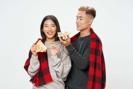 happy young people with slices of pizza and a warm plaid