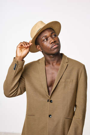 A gentleman of African appearance in a hat and jacket looks away