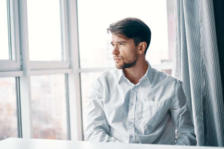 A puzzled man in a shirt looks out the window and sits