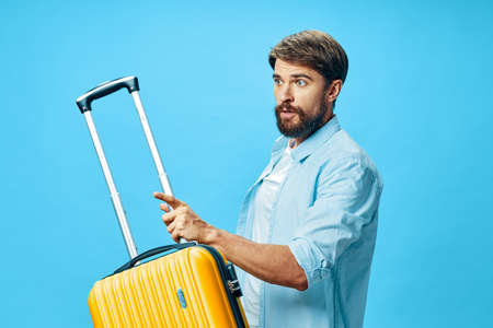traveler with a yellow suitcase looks away in surprise on a blue background
