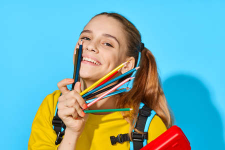 schoolgirl with colored pencils laughs at the camera and holds a pencil case