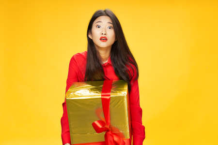 gift box with a red bow in the hands of a surprised woman Archivio Fotografico