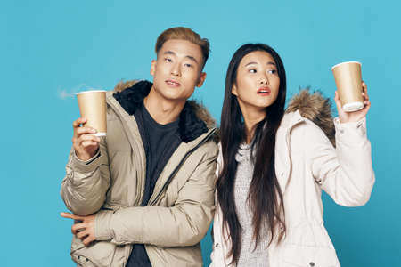Hot drink in the hands of a young couple of asian appearance lifestyle