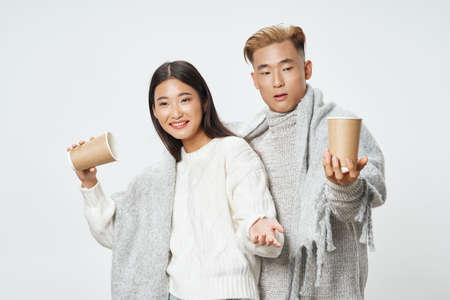 Cups of coffee in the hands of a young couple of Asian appearance socializing