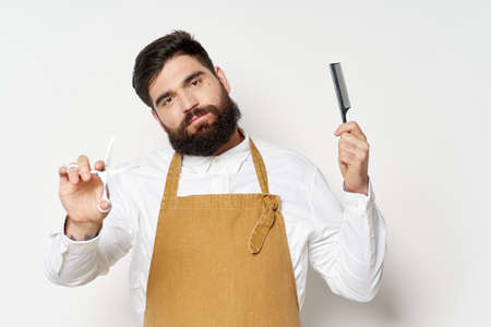 Male hairdresser with scissors and comb