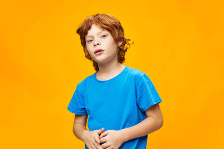 A boy with red hair in a blue T-shirt, I put my hands together