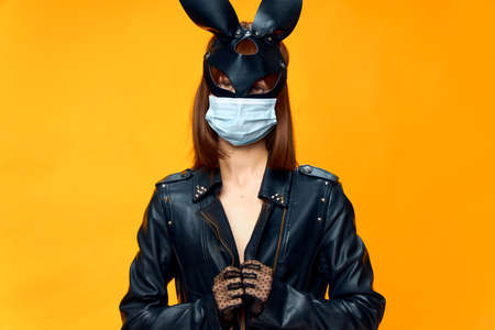 Female rabbit mask posing sexually in a medical mask from coronavirus