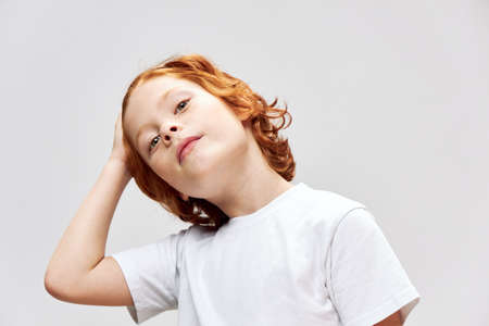 Cute redhead boy holding his hand on his head white t-shirt cropped view Reklamní fotografie