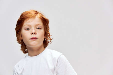 cute red-haired boy with freckles on face wearing white t-shirt gray isolated background