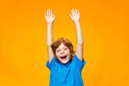 Red-haired boy with his hands up on a yellow background