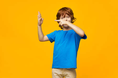 The red-haired boy shows his palm and gestures with his hands on a yellow background