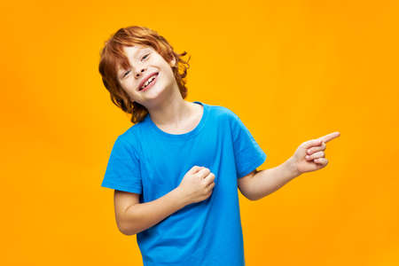 Happy child in a blue T-shirt points to the side and smiles