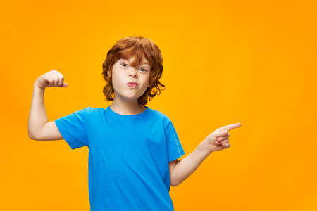 red-haired boy is playing pranks on a yellow background and points his finger to the side, free space