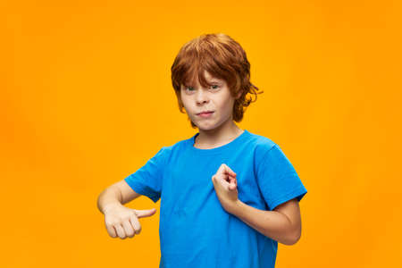 A boy with freckles shows his thumb to himself and a blue t-shirt
