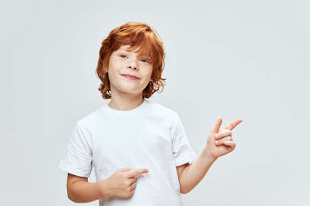 portrait of a red-haired boy smile emotions gestures hands shows on the side studio