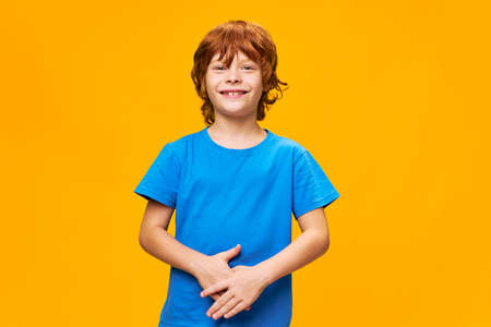 boy red hair blue t-shirt yellow isolated background freckles and a beautiful smile